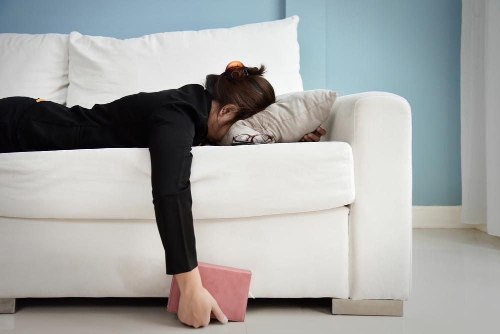 椅子に突っ伏して寝る女性