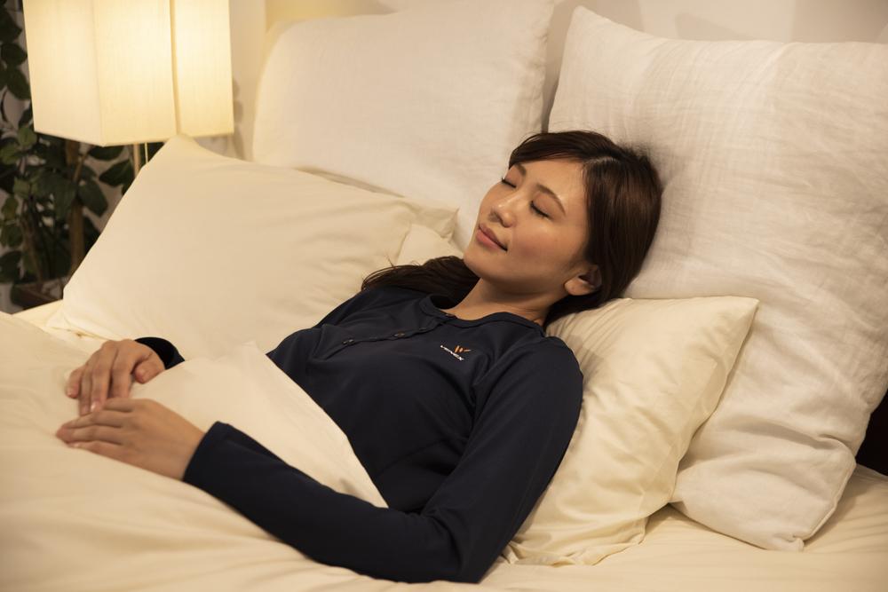 リカバリーウェアを着て寝る女性