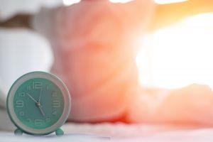 朝日で起床する人と時計